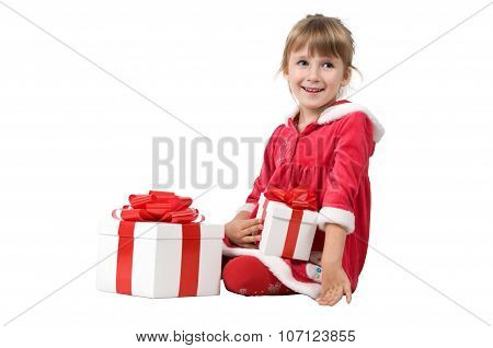 Little Girl Sits With A Gift Box On A White Background