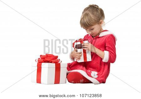 Little Girl Wearing A Christmas Costumes. She Sits On A White Background And Opens A Cardboard Box W