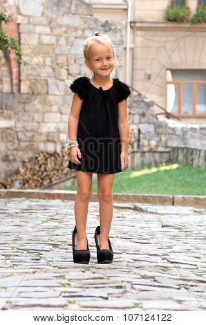 Little Girl Dressed Like An Adult Woman. In High-heeled Shoes
