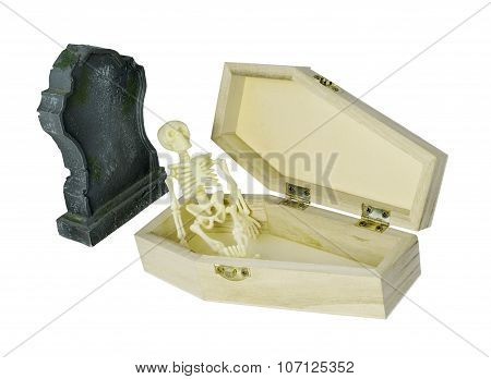 Skeleton Sitting In Coffin Next To Gravestone