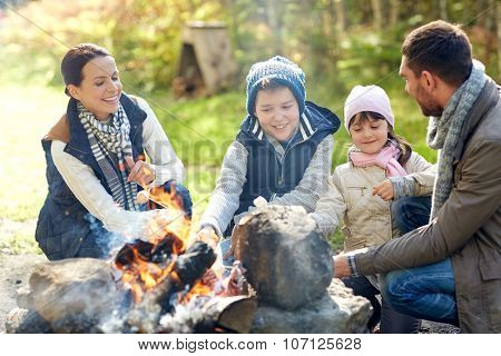 camping, travel, tourism, hike and people concept - happy family roasting marshmallow over campfire