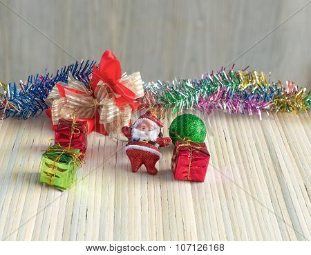 Santa Claus Doll Against Gift Box With Ball On Wood Background