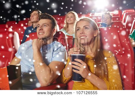 cinema, entertainment and people concept - happy friends or couple with popcorn and lemonade drink watching movie in theater with snowflakes