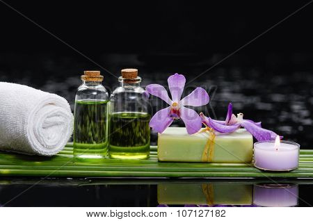 Beautiful orchid with candle ,leaf, oil,towel and therapy stones