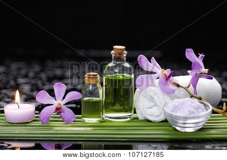 Set of orchid with long stem and towel,candle on wet background