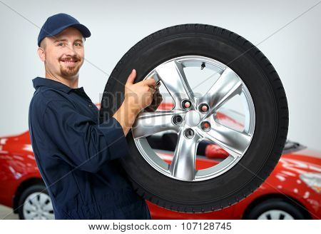 Smiling car mechanic with a tire over red car background.