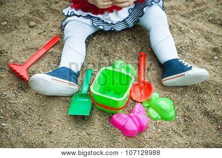 child playing in the sandbox shovel