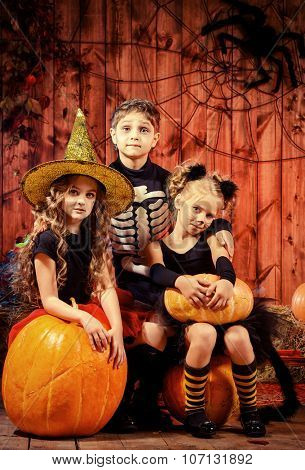 Group of children in halloween costumes celebrating halloween in a wooden barn with pumpkins. Halloween concept.
