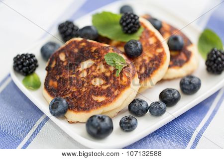 Quark cheese fried cakes with blueberry. Traditional Russian sweet syrniki.