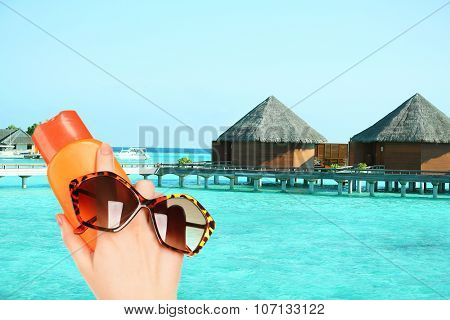Bottle of suntan cream and sunglasses in hand on hotel background
