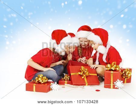 Christmas Children Open Presents, Kids In Santa Hat, Group Of Girls And Boys
