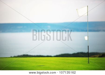 Flag, Hole And Golf Ball On The Green Field.