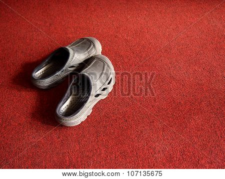 Pair of rubber shoes on a red carpet