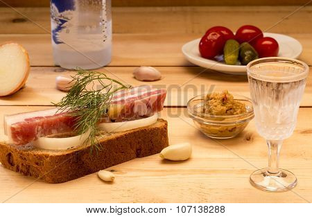Sandwich with spiced lard served with garlic, onions, mustard, pickles, tomatoes and cold vodka
