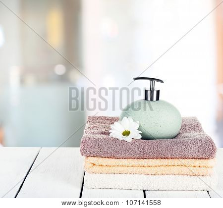 Soft towels with dispenser and flower in bathroom