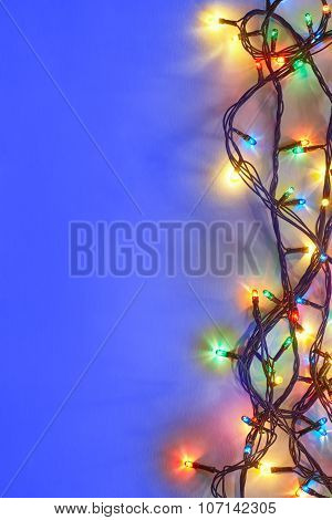 Christmas Lights On Blue Background With Copy Space.