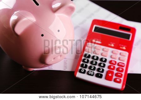 Pig moneybox and calculating equipment on desk closeup