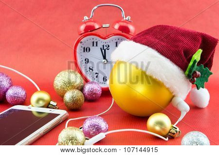 Christmas Ball With Santa's Hat, Smartphone With Earphones And Clock, On Red