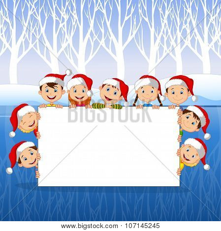 Little Kids with a blank sign and Christmas hats with winter background