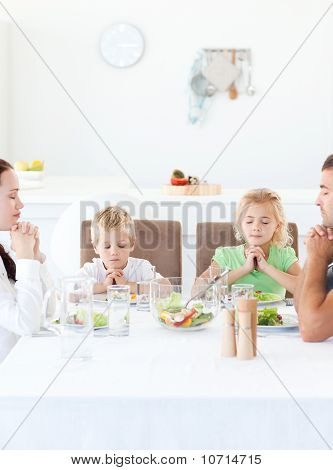 Parents And Their Children Praying During Their Lunch