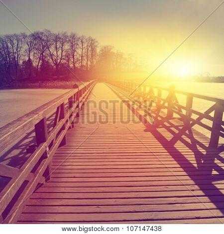 Wooden bridge over frozen river at sunset.