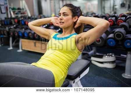 Determined woman doing sit ups at the gym
