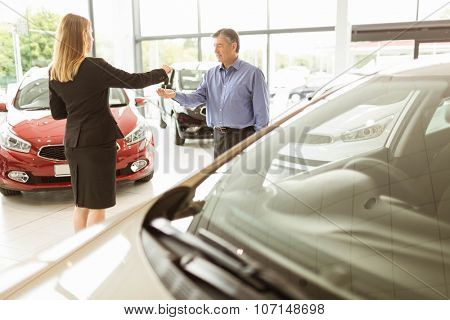 Saleswoman giving car keys while shaking hand of a client at new car showroom