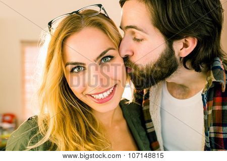 Hipster kissing his pretty colleague in casual office
