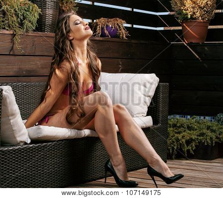 beauty young real woman after spa in bikini and robe at hotel resort, on terrace enjoying warm sun s