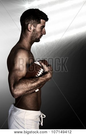 Side view of shirtless man holding ball against spotlight