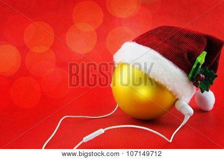 Christmas Ball With Santa's Hat And Earphones, On Red With Bokeh Lights