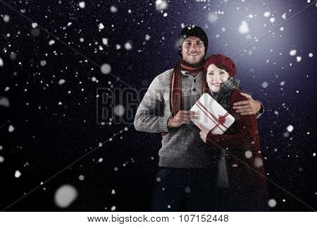 Couple smiling and holding gift against snow