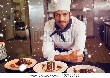 Snow against happy chef looking at camera behind counter of desserts
