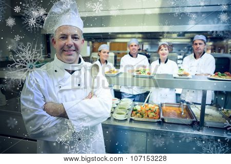 Snow against experienced head chef posing proudly in a modern kitchen