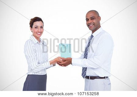Business colleagues holding plant and looking at camera against gift bag