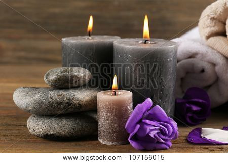 Alight wax grey candles with flowers, towels and pebbles on wooden background - relax set