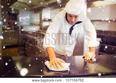 Snow against male cook wiping the kitchen counter