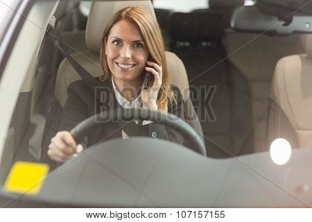 Smiling businesswoman having a phone call while sitting in a car at new car showroom