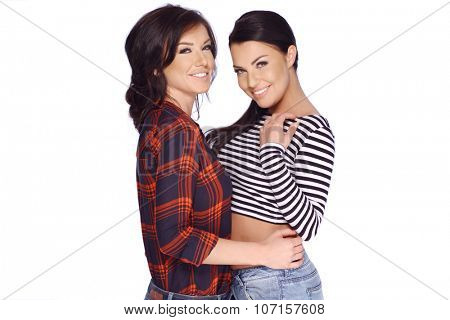 Two Brunette Girls in Casual Clothes Posing in Studio on Clean Background  Smiling
