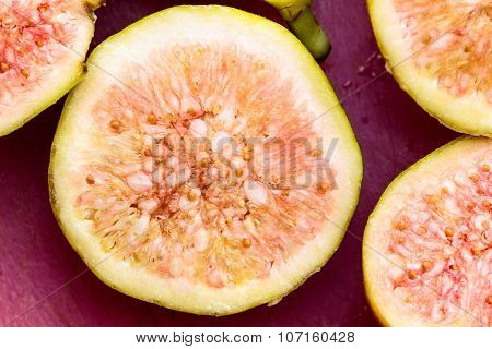 Health Concepts: Cross section cut of a freshly plucked fig kept on a plain background