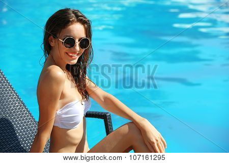 Young woman enjoying on sunbed at swimming pool
