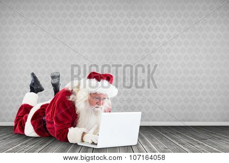 Santa lies in front of his laptop against room with wooden floor