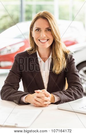 Smiling saleswoman working at her desk at new car showoroom