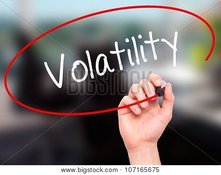 Man Hand writing Volatility with black marker on visual screen.