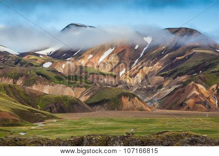 Early summer morning in the National Park Landmannalaugar, Iceland. Snow lies in the hollows of multicolored rhyolite mountains