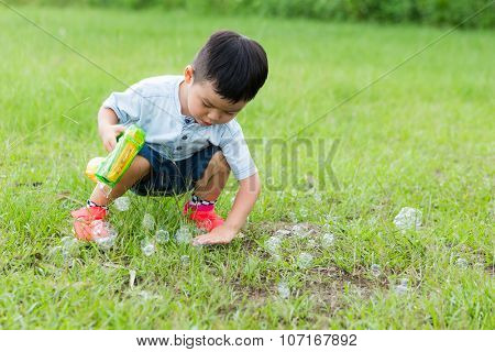 Little boy squat down and touch the bubble on the land