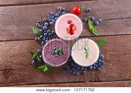 Tasty blueberry, strawberry and milk yogurts with berries and mint around on wooden background