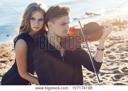 violinist and girl,  young man plays on the background of  sea