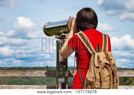 Young Woman Looking Through Tourist Telescope, Exploring Mountain Landscape.