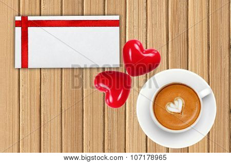 Greeting Card With Red Ribbon, Coffee And Two Red Hearts On Wooden Table